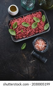 Raw fresh beef mincemeat with seasonings over dark brown stone background, vertical shot with space, above view