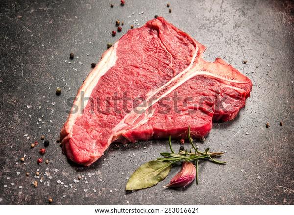 roh frisches Rindfleisch, T-Bein-Steak und Würzmittel auf dunklem Hintergrund