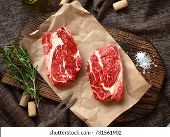 Raw fresh Chuck roll steak with herbs and salt on a cutting Board top view