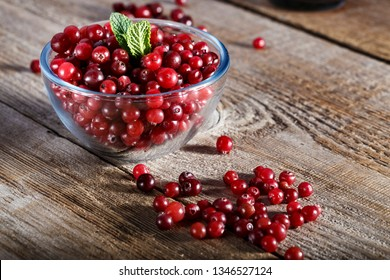 raw fresh cranberries in a plate on a wooden table. space for text