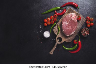 Raw fresh cross cut veal shank and ingredients for Osso Buco cooking on black background