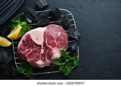 Raw fresh cross cut veal shank with parsley and lemon. Above view on a black stone background with charcoals, copy space