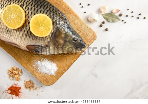 Raw fresh fish (carp) with lemon and spices on light vintage background with copy space.