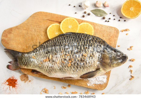 Raw fresh fish (carp) with lemon, garlic and spices on wooden cutting board on light vintage background with copy space. Healthy food and cooking.