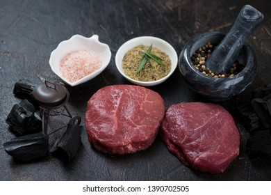 Raw fresh marbled beefsteaks with condiments, charcoal and a decorative grill on a dark brown stone background