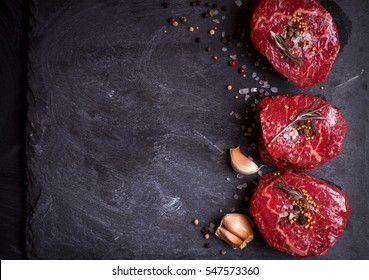 Raw fresh marbled filet mignon steaks with seasonings ready for roasting on black concrete background. Filet mignon steaks with herbs, garlic, pepper, salt and ingredients. Space for text. Top view