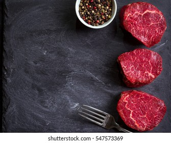 Raw fresh marbled filet mignon steaks and fork, ready for roasting on black concrete background. Raw juicy filet mignon steaks. Space for text. Top view. Food frame