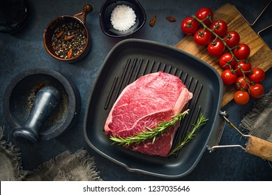Raw Fresh Marbled Meat Beef on a grill pan ready for cooking on a blue concrete background top view