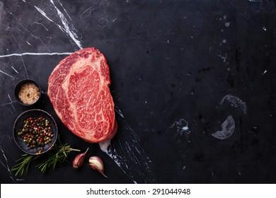 Raw fresh marbled meat Black Angus Steak Ribeye and seasonings on dark marble background