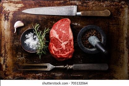 Raw fresh marbled meat Steak Rib eye Black Angus, seasoning and fork and knife on dark background