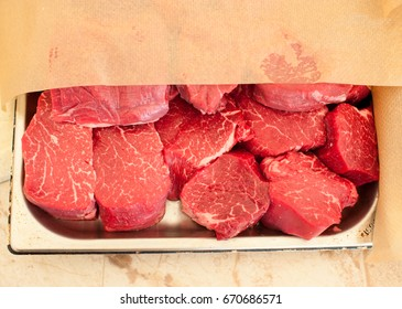 Raw fresh meat. Chopped steaks medallions of marbled veal on a pallet