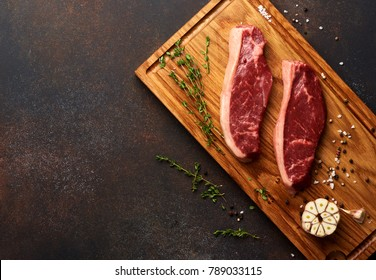Raw fresh meat Picanha steak, traditional Brazilian cut with thyme, garlic, and black pepper on wooden board. Top view.