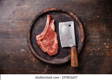 Raw fresh meat Ribeye Steak and meat cleaver on dark background