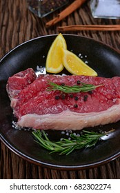 Raw fresh meat steak in the black dish with rosemary and spices on wooden table. Decorated with lemon and herb. Homemade Cooking. Concept about food preparation in the kitchen
