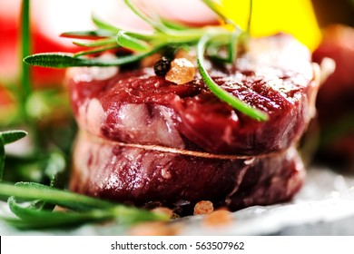 Raw fresh meat Steak filet mignon and rosemary on cooking paper background