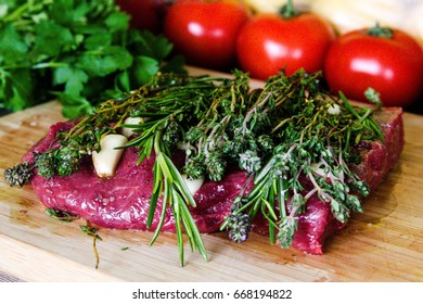 Raw fresh meat steak with herbs and tomatoes