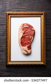 Raw fresh meat Striploin steak in Gold picture frame on Black Burned wooden background