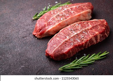 Raw fresh meat Top Blade steaks on dark background. with copy space