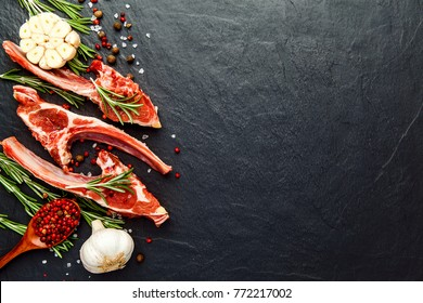 Raw fresh meat, uncooked lamb ribs with ingredients for cooking. On dark table, copy space top view