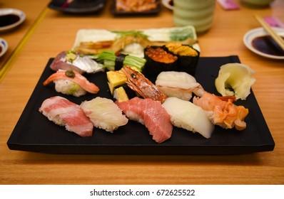 Raw and fresh Mix sushi set in black plate include Otoro (Fatty blue fins tuna), Uni (urchin), Unagi (eel), salmon and others  - Japanese food set style at Tsukiji fish market, Tokyo