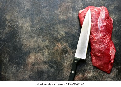 Raw fresh organic beef with knife on a dark slate, stone, concrete or rusty metal background.Top view with copy space.