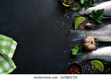 Raw fresh organic sea bass fish with spices and ingredients for making on a black slate, stone or concrete background. Top view with copy space.