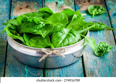 raw fresh organic spinach in a bowl on wooden rustic table