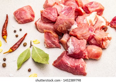 Raw fresh pork shoulder, cut into pieces with spices. Cooking healthy protein food concept. Dried bay leaves, chilli and black pepper, allspice, garlic pieces. Concrete background, close up
