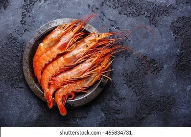 Raw fresh Prawns Langostino Austral on metal plate on black background