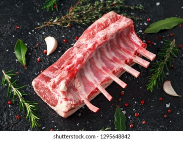 raw fresh rack of lamb with green herbs.