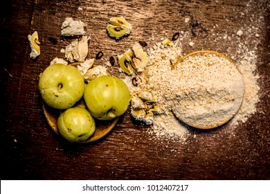 Raw fresh ripe Phyllanthus emblica,amla or Indian gooseberry with its powder on wooden surface.