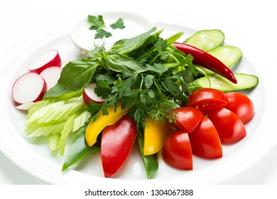 Raw fresh sliced vegetables close up on a plate isolated on white