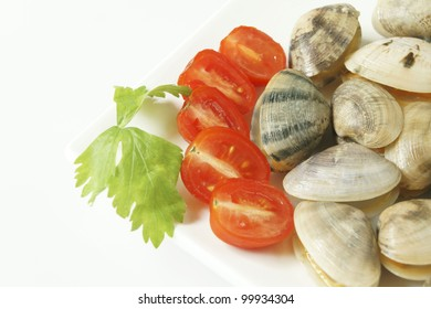 Raw fresh small clams in isolated background with tomato