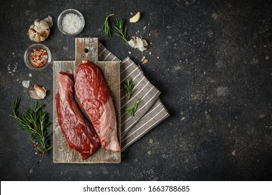 Raw Fresh Steak Sirloin Flap Served with Rosemary, garlic and spices on Wooden cutting Board. Black Angus Beef Meat. Top View, place for text