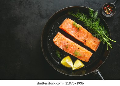 Raw fresh tasty salmon steaks placed on pan with ingredients. Ready to cook. Slate background. View from above with copy space.