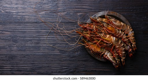 Raw fresh Tiger Prawn Shrimp in metal plate on burned black wooden background copy space
