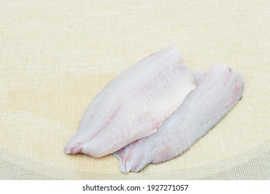 Raw fresh tilapia fillets with seasonings ready to be cooked,