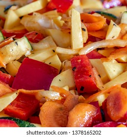 Raw fresh vegetables cut for further processing, mixed and topped with an oily spice mixture.