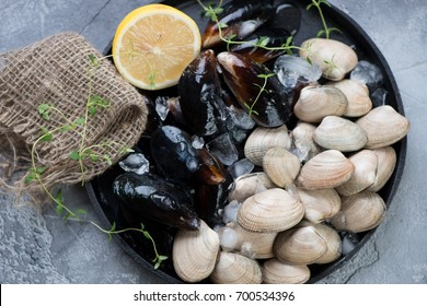 Raw fresh vongole clams and mussels on ice in a metal plate, above view, horizontal shot