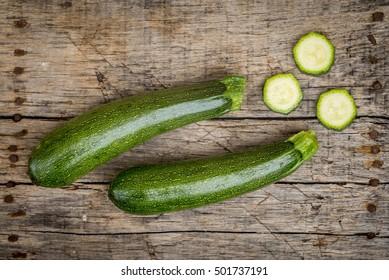 Raw fresh zucchini on a wooden background