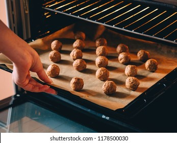Raw frozen meat balls on baking sheet with paper.