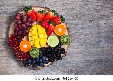 Raw fruit and berries platter, mango, kiwis, strawberries, blueberries, blackberries, red currants, grapes, top view, copyspace for text