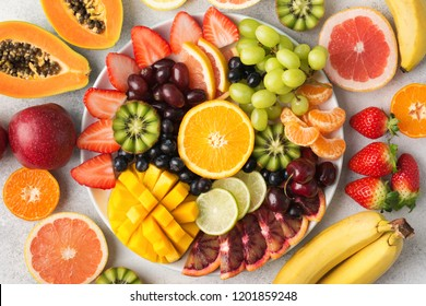 Raw fruits berries platter, mango, oranges, kiwi strawberries, blueberries grapefruit grapes, bananas apples on the white plate, on the off white table, top view, selective focus