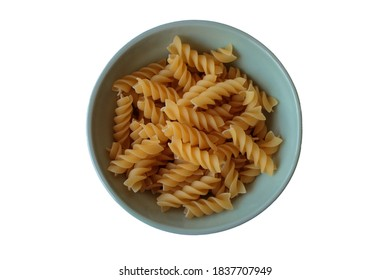 Raw fusilli pasta in a ceramic green plate on a white table. Top view. İsolated.