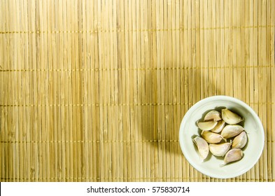 Raw Garlics on the Bamboo Background. Good Gerb To protect People from Flu. Favolite to cook in Thai Food and Asia Fod.