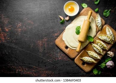 Raw gedza dumpling. A homemade dumplings gedza with meat. On dark rustic background
