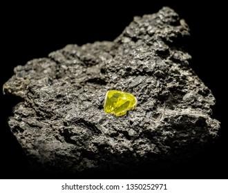 A raw gemstone in stone. Rock with precious diamonds on black background.  A discovery of luxury jewel in Kimberley mine.