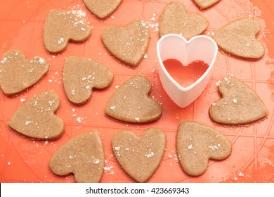 Raw gingerbread dough prepared for cookies. Heart shaped cookies with plastic cutter on silicon baking mat. Top view