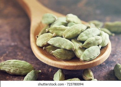 Raw green cardamom pods in wooden spoon on rustic background