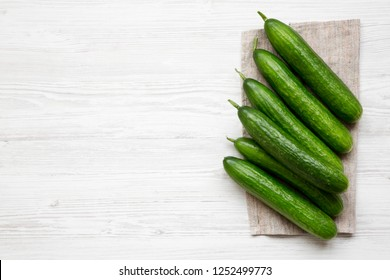 Raw green cucumbers, top view. Flat lay, overhead, from above. Copy space.